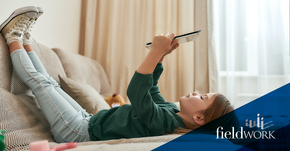 A small child lays on a bed watching a tablet device.